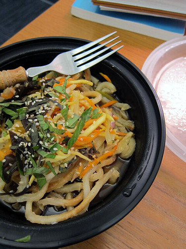 To-go bowl filled with thick udon noodles and sliced veggies in a thin broth.