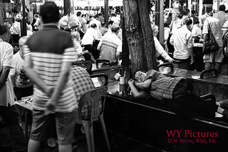 Man Sleeping In The Crowd In Chinatown