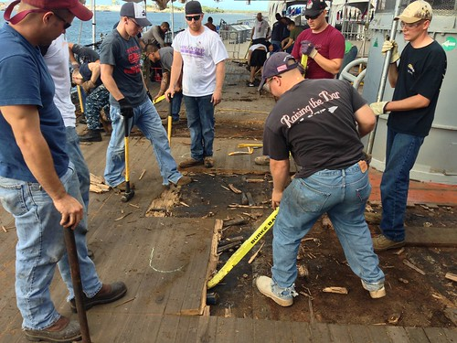 Sailors work to restore and salvage the teak decks on USS MISSOURI