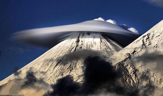"""2015年10月22日報導(具體拍攝時間不詳),俄羅斯,乍一看上去,這些盤旋在俄羅斯勘察加火山山頂的奇異的雲就像是UFO一般,而其實它們是""""莢狀雲"""",也叫飛碟雲,狀如飛碟,常被誤認為外星飛船或不明飛行物。俄攝影師Vladimir Voychuk拍攝了這些令人瞠目的奇異雲照片。他說,這不是他第一次看到這些""""莢狀雲""""天象了,但是他第一次能拍下它們的照片。"""