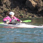Deb in a slalom boat on the Swellies wave - By Sea Kayaking Anglesey