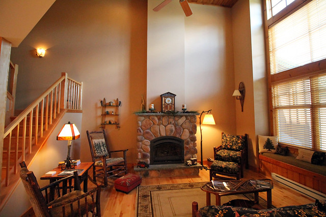 Great room with vaulted ceilings, stone fireplace, hardwood floors, window seat overlooking the back yard and balsams.