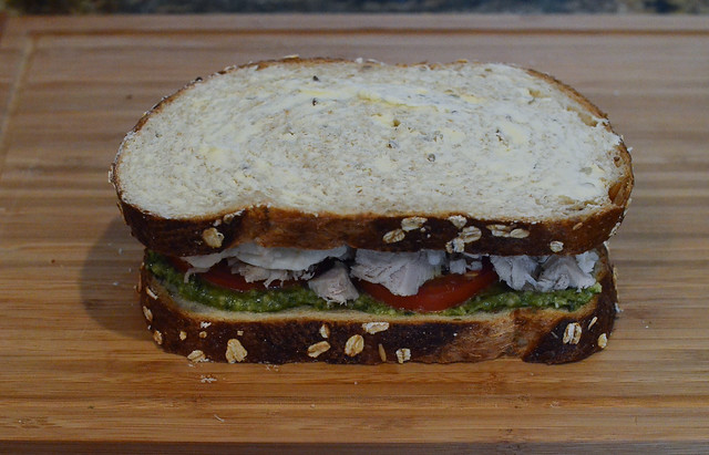 The second piece of bread is placed on top of the sandwich, butter side up.