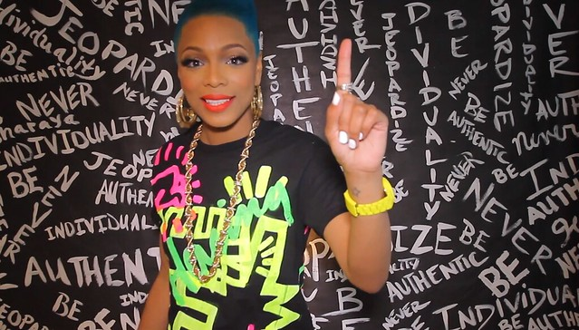 Sharaya J, a black woman with bright blue hair, flashes a number one sign