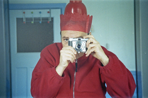 reflected self-portrait with Kodak Retinette I camera and compound red hat by pho-Tony