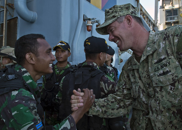 JAVA SEA - Electronics Technician 1st Class Anthony Nekervis, assigned to Maritime Civil Affairs and Security Training (MCAST) Command, shakes hands with a member of the Indonesian special forces boarding team Kopaska.