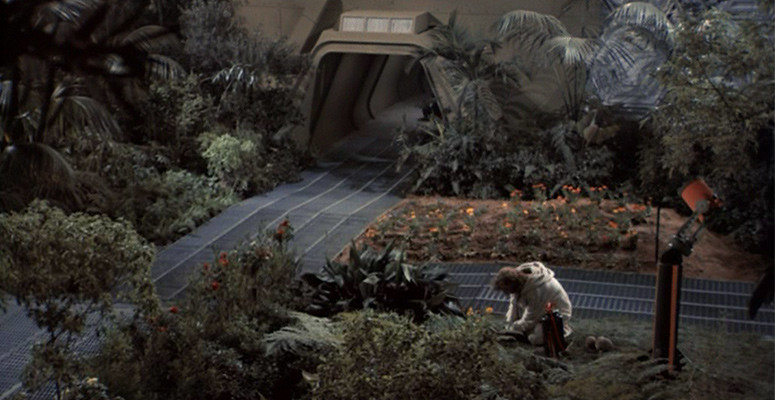 Screenshot from film Silent Running. Man, kneeling on the ground, working in garden on spaceship.