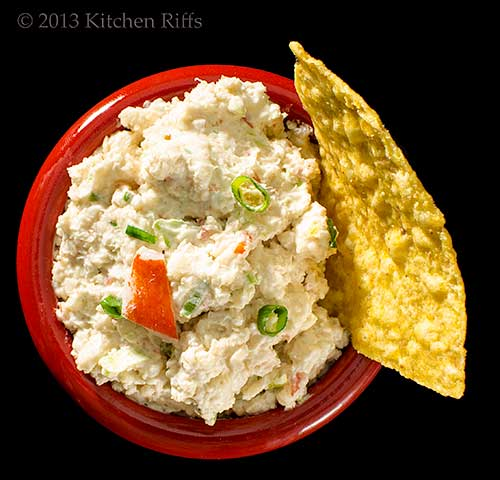 Crab Rangoon dip in red bowl with chip, overhead view on black