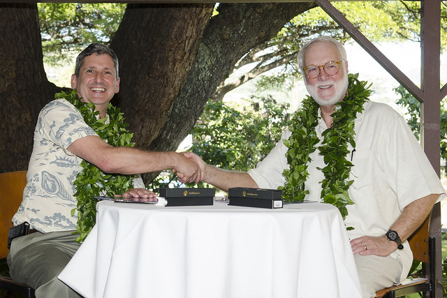 two men shaking hand across a table