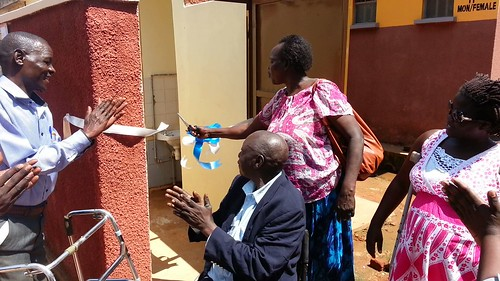 The Gulu Municipal Council Secretary for Disability does the honors as the ribbon is cut