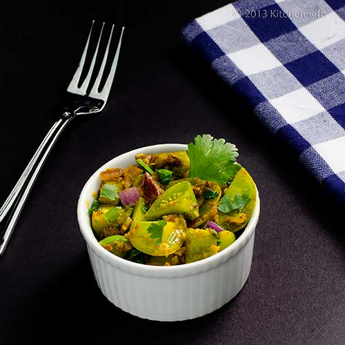 Curried Green Tomatoes in ramekin with napkin and fork in background