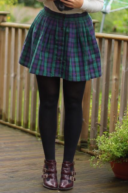 Snood, white jumper, tartan skirt, cut out boots
