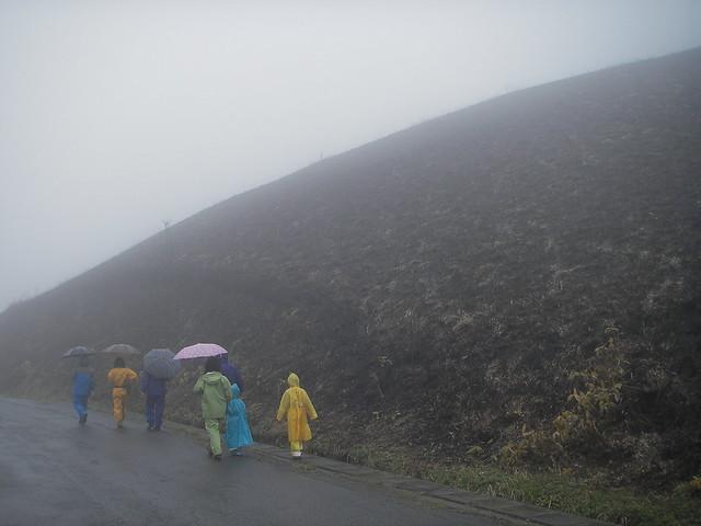 アスファルトの道を出発!白い景色の中に,黒く焼けた山肌が浮かび上がる.