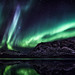 Northern lights display over mountains and lake by @ilovegreenland