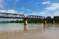 The infamous Bridge over the River Kwae seen from the nearby floating restaurant, Kanchanaburi, Thailand