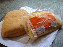 "A semicircular pastry item in a clear plastic bag with a label reading ""First Choice Bakers Chicken Pattie"", resting on top of a flat and roughly semicircular white bread roll which itself is on top of a white paper bag."