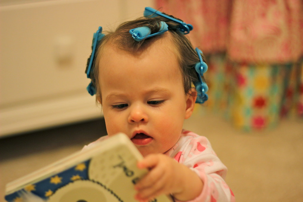 Baby girl reading with hair in curlers
