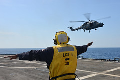 Boatswain's Mate 1st Class James Small directs a Royal Malaysian Navy Super Lynx as it does touch and go training on the flight deck of USS Freedom (LCS 1), June 18 in the South China Sea. (U.S. Navy photo by Mass Communication Specialist 1st Class Cassandra Thompson)