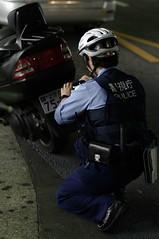 路上駐車中の二輪車を撮る警察官を撮る