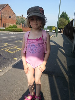 Amber at the bus stop in her swimming costume and my hat