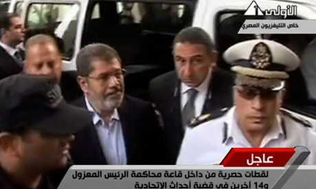 Deposed Egyptian President Mohamed Morsi being brought into court at the police academy. Morsi was overthrown by the military on July 3, 2013. by Pan-African News Wire File Photos