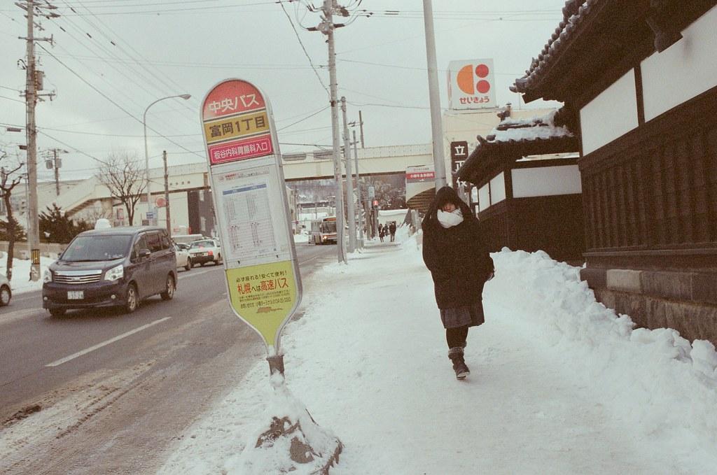 小樽 Otaru 北海道 / Fujifilm 500D 8592 / Nikon FM2 這也是繼續對著迎面而來的路人拍攝,那時候算是第一次來到有下雪的地方,不是很清楚在雪地生活的方式是什麼,所以看著當地人的穿著、步伐、應對方式都感到相當新奇。  剛好這兩張都帶著口罩,好像應該用這樣的方式防止臉凍傷齁!  Nikon FM2 Nikon AI AF Nikkor 35mm F/2D Fujifilm 500D 8592 1119-0025 2016/02/02 Photo by Toomore