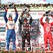 Will Power, Justin Wilson, and Dario Franchitti raise their trophies in Victory Circle