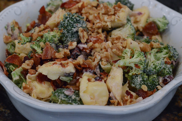 A close up of a bowl of tortellini salad topped with walnuts.