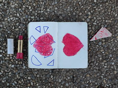 "Broken Heart Tangram in my Book of Playing ""Homo Ludens"" - Old Lipstick, used for drawing - Broken Off Corner from the drawing ""Stubbed ~ Gerodet beim Narrenturm; Ein Leidensblatt"" on the Paper from the Abandoned Cement Plant - MirrorGround Steinhof"