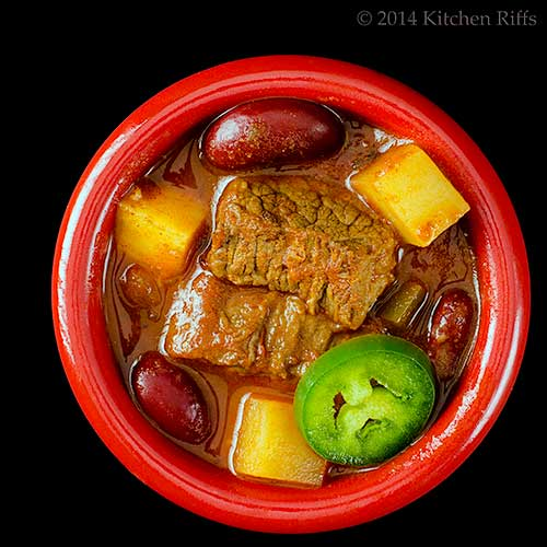 Meat and Potatoes Chili in bowl with jalapeño garnish, overhead view on black