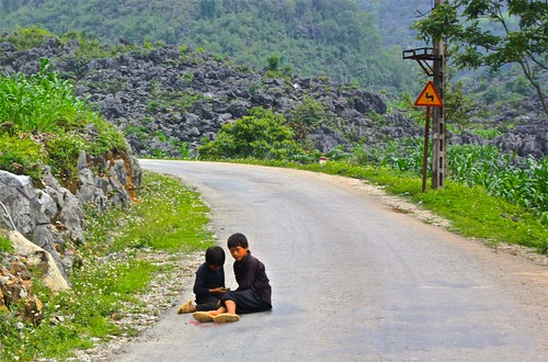 two Black Hmong boys take a break on the road