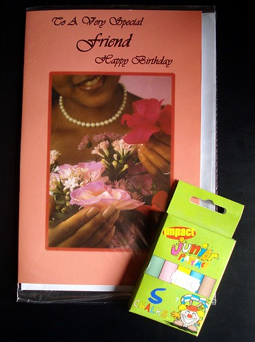 "A small green cardboard packet of coloured chalks, lying on top of a birthday card with a photo of a black woman wearing a string of pearls and holding several flowers. The surround of the card is peach-coloured, and printed in cursive letters at the top is ""To A Very Special Friend / Happy Birthday""."