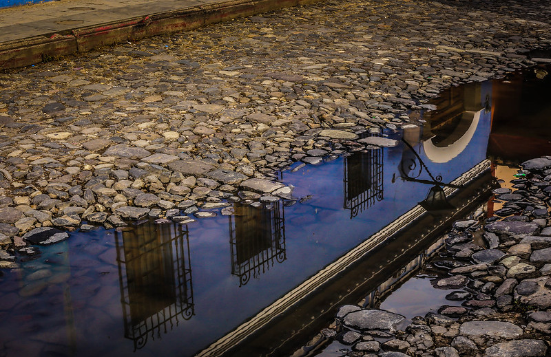Reflection of blue building in puddle