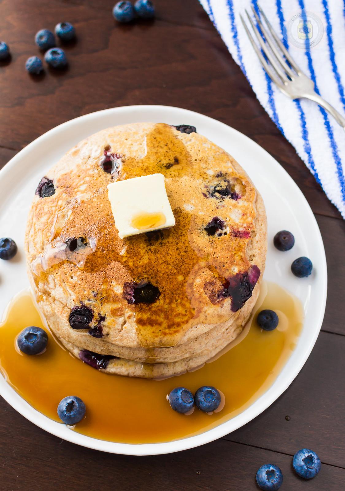 stack of blueberry pancakes with butter sitting in a puddle of pancake syrup