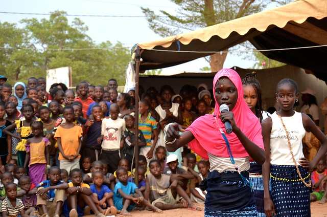 A young girl talks into a microphone in front of a crowd of young people.