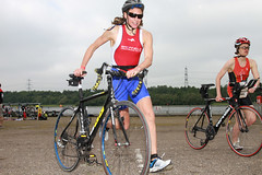 image of 2 female triathletes running with their bikes