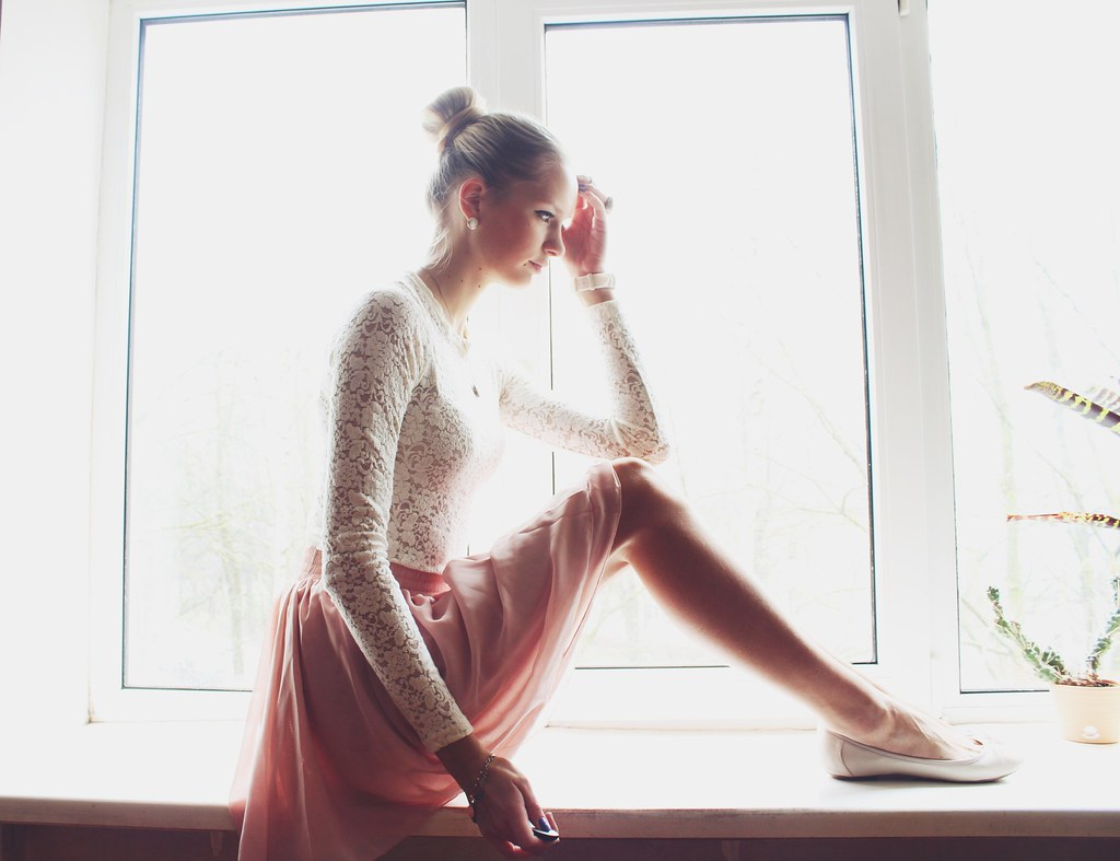 Newest outfit post on call me maddie: a blonde girl sitting on a window sill, wearing a white lace blouse, light pink candy skater skirt from Ebay, rings from H&M. Ballerina look a like outfit, how to make a high tight bun,