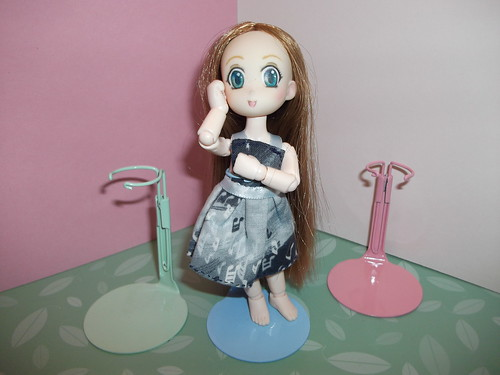 Karen and her tiny doll stands.