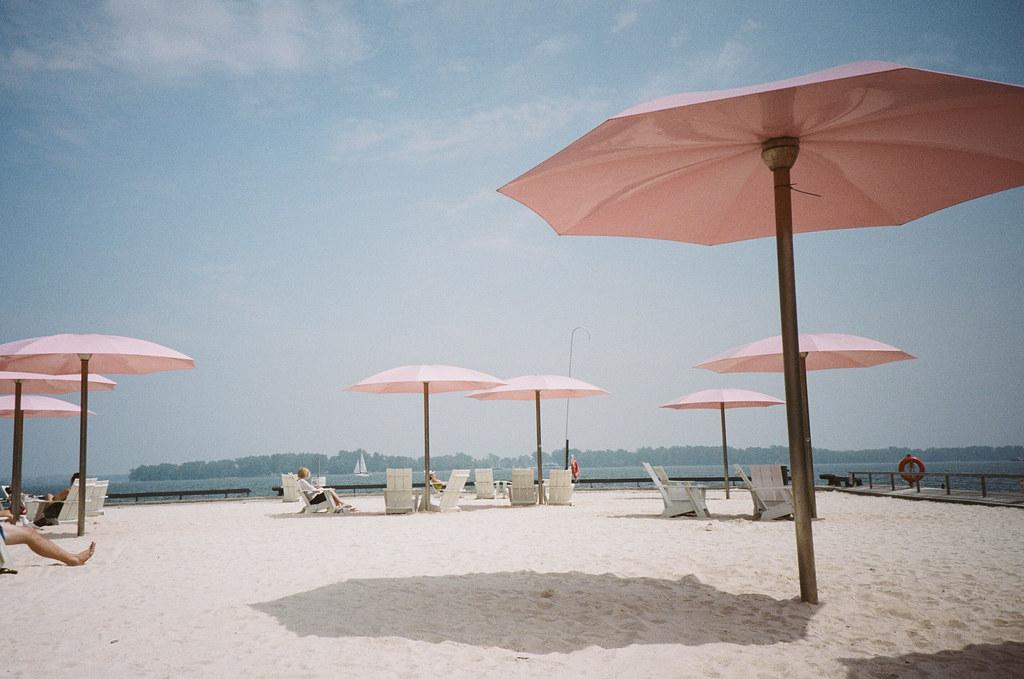 tumblr, images, photos, photography,lightsugar beach, pink, sand, umbrella, happy, blue skies, water, sailboats, sailing