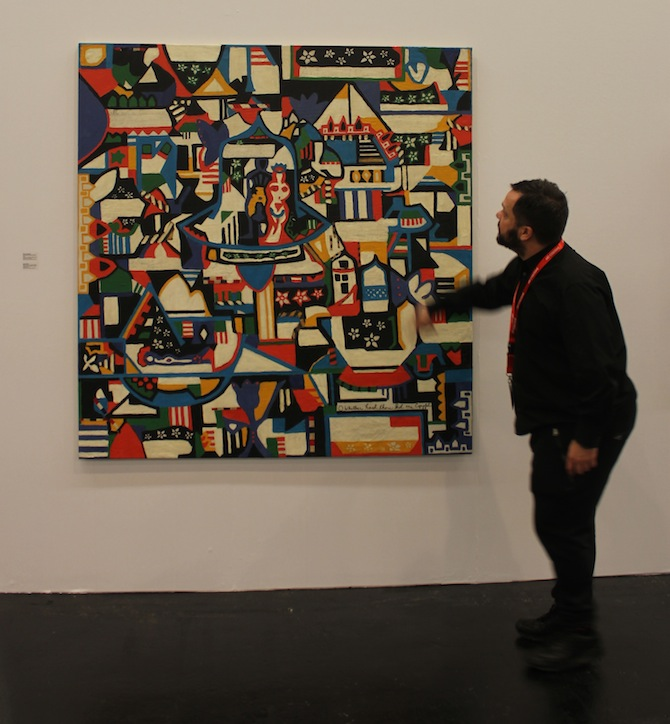 Javier Peres in front of Dorothy Iannone painting at booth Peres Projects