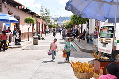 Young shoe shiners and a street food seller on the streets of San Cristobal