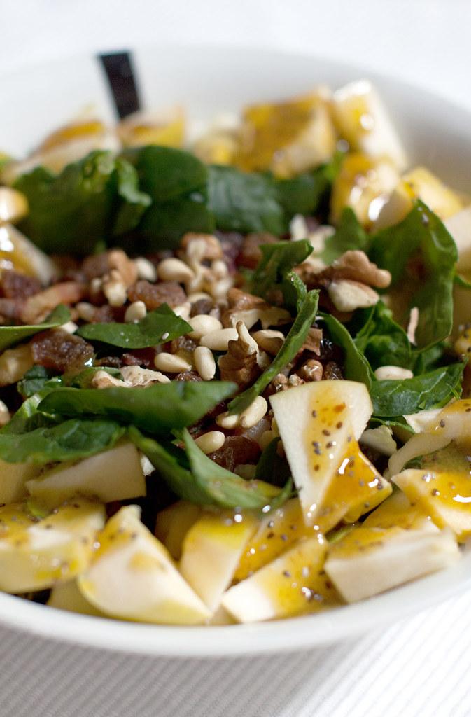 Detalle de ensalada sin almidón de espinacas, manzana y frutos secos