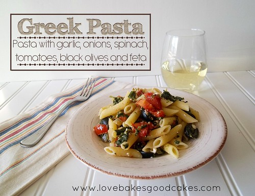 Greek Pasta in bowl with fork and a glass of wine.