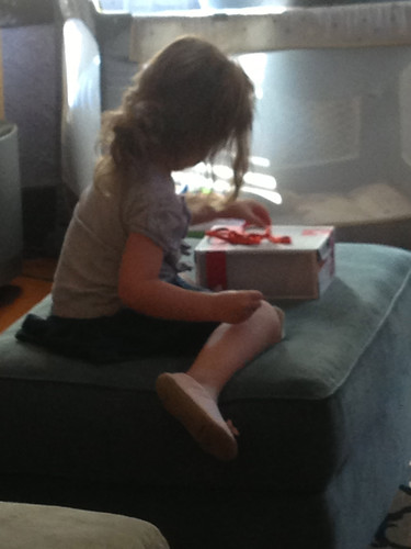 Trying so hard to tie her shoe box