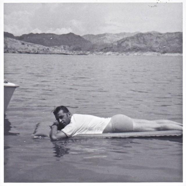 Vintage 1960s Photo: Man Lying On A Raft On A Lake