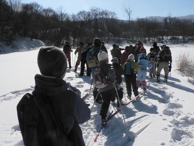 自然館の裏の丘に上がる.クロカンスキー,かんじき,スノーシューなど,装備はさまざま.