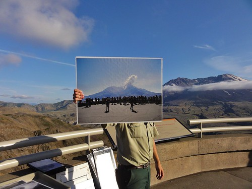 Ranger holding a photo of Mount St. Helens, erupting during another ranger's talk.