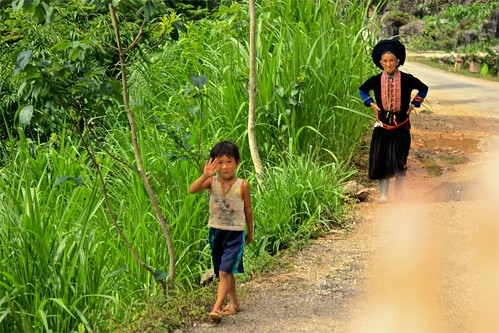 a young boy waves as we pass him and his grandmother in Black Hmong traditional dress