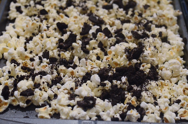 Crushed Oreos are sprinkled on top of the popcorn mixture.
