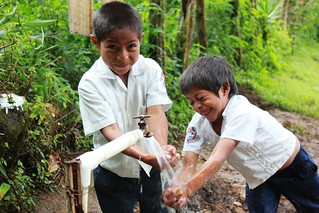 Two little boys laugh as they wash their hands